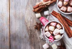 热巧克力用蛋白软糖和香料在土气木桌上 免版税库存照片