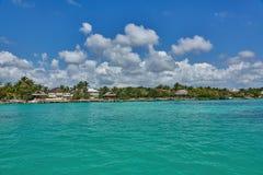 热带别墅和平房如被看见从绿松石海洋典型的加勒比岛生活 免版税库存照片