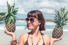 热带夏天妇女用两个菠萝在她的手上 户外,海洋,天堂,巴厘岛 免版税库存照片