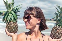 热带夏天妇女用两个菠萝在她的手上 户外,海洋,天堂,巴厘岛 免版税图库摄影