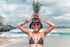 热带夏天妇女用在她的头的菠萝 户外,海洋,自然 巴厘岛天堂 免版税库存照片