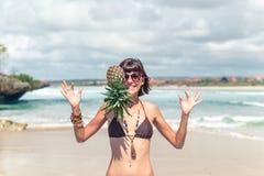 热带夏天妇女用在她的头的菠萝 户外,海洋,自然 巴厘岛天堂 免版税库存图片
