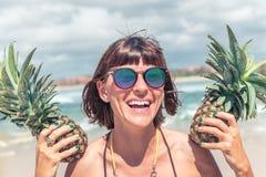 热带夏天妇女画象用两个菠萝 户外,户外,海洋,自然 巴厘岛天堂 库存照片