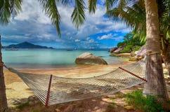 热带天堂-在可爱的海滩的吊床在棕榈树之间的海边 库存图片