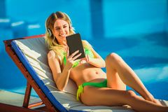 热带太阳的妇女在游泳池附近 免版税图库摄影