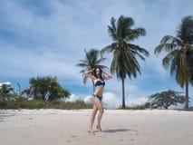 热带富饶海滩的愉快的亭亭玉立的年轻女人 库存照片