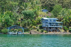 热带岸的沿海房子与在船坞的小船 免版税库存照片