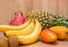 热带新鲜水果集合和汁圆滑的人隔绝有木背景 图库摄影