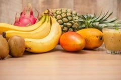 热带新鲜水果集合和汁圆滑的人隔绝有木背景 库存照片