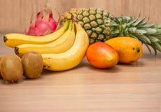 热带新鲜水果集合和汁圆滑的人隔绝有木背景 免版税图库摄影