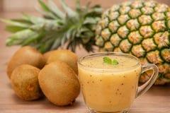 热带新鲜水果集合和汁圆滑的人隔绝有木背景 免版税库存照片