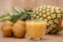 热带新鲜水果集合和汁圆滑的人隔绝有木背景 免版税库存图片