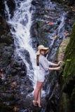 热带旅行 帽子的少妇享受瀑布视图的 库存照片