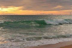 热带日落和波浪 免版税库存图片