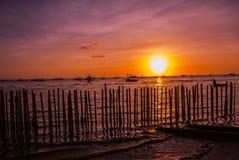 热带横向的日落 篱芭和海 使白色靠岸 博拉凯 菲律宾 库存照片
