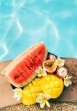 热带水果和花在水池附近 免版税库存照片