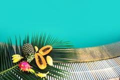 热带水果在棕榈叶说谎在水池附近 免版税库存照片