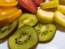 热带水果的混合:猕猴桃、桔子、香蕉和草莓 免版税库存图片