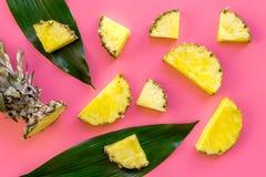 热带水果背景 在大叶子前面的Pinneapple切片在桃红色背景顶视图 免版税库存图片