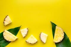 热带水果背景 在大叶子前面的Pinneapple切片在黄色背景顶视图copyspace 免版税图库摄影