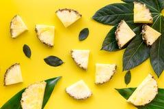 热带水果背景 在小和大叶子前面的Pinneapple切片在黄色背景顶视图 库存图片