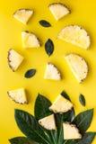热带水果背景 在小和大叶子前面的Pinneapple切片在黄色背景顶视图 免版税库存照片