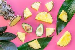 热带水果背景 Pinneapple和鳄梨片,在桃红色背景顶视图的大叶子 库存照片