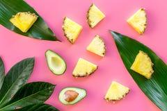 热带水果背景 Pinneapple和鳄梨片,在桃红色背景顶视图的大叶子 免版税库存图片