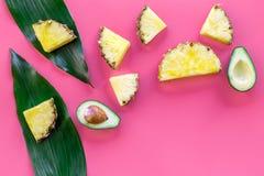 热带水果背景 Pinneapple和鳄梨片,在桃红色背景顶视图copyspace的大叶子 免版税图库摄影