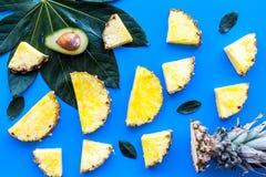热带水果背景 Pinneapple和鳄梨片,在蓝色背景顶视图的大叶子 免版税库存图片