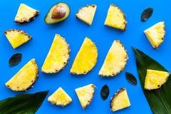 热带水果背景 Pinneapple和鳄梨片,在蓝色背景顶视图的大叶子 库存照片