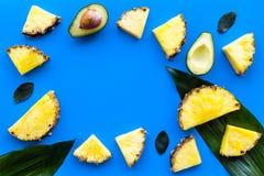 热带水果背景 Pinneapple和鳄梨片,在蓝色背景顶视图copyspace的大叶子 免版税图库摄影