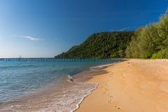 热带海岛金黄沙滩有树木丛生的陆岬的 免版税库存图片