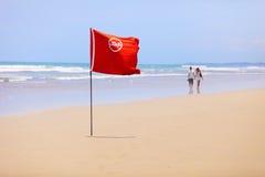热带海滩和一面红旗。 不要游泳! 库存图片