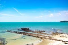 热带海滩在晴天有蓝天背景和白色离开了沙子 免版税图库摄影