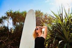 热带海滩的冲浪者女孩 免版税库存照片