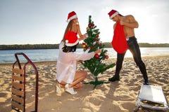热带海滩的圣诞老人的辅助工和圣诞老人 免版税库存照片