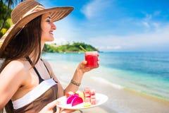 热带海滩的妇女吃果子早餐的 库存照片