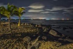 热带海滩在与城市的晚上在背景- HDR中点燃 库存图片