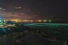 热带海滩在与城市的晚上在背景- HDR中点燃 库存照片