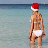热带海滩的圣诞老人女孩。美丽的白肤金发的少妇 免版税库存图片