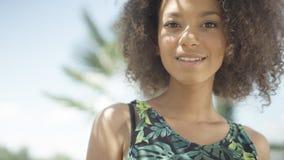 热带海滩的微笑对照相机的美丽的少年美国黑人的女孩画象  免版税库存照片