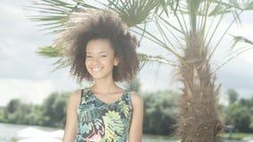 热带海滩的微笑对照相机的美丽的少年美国黑人的女孩画象  图库摄影
