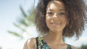 热带海滩的微笑对照相机的美丽的少年美国黑人的女孩画象  免版税图库摄影