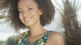 热带海滩的微笑对照相机的美丽的少年美国黑人的女孩画象  库存图片