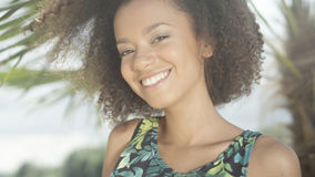热带海滩的微笑对照相机的美丽的少年美国黑人的女孩画象  免版税库存图片