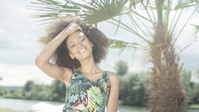 热带海滩的微笑对照相机的美丽的少年美国黑人的女孩画象  库存照片