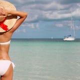 热带海滩的性感的女孩。有太阳帽子的美丽的少妇 免版税库存图片