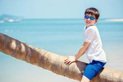 热带海滩的逗人喜爱的小男孩坐棕榈树 库存图片