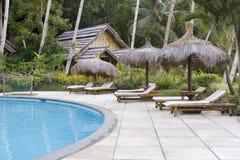 热带游泳池边的手段 免版税库存图片